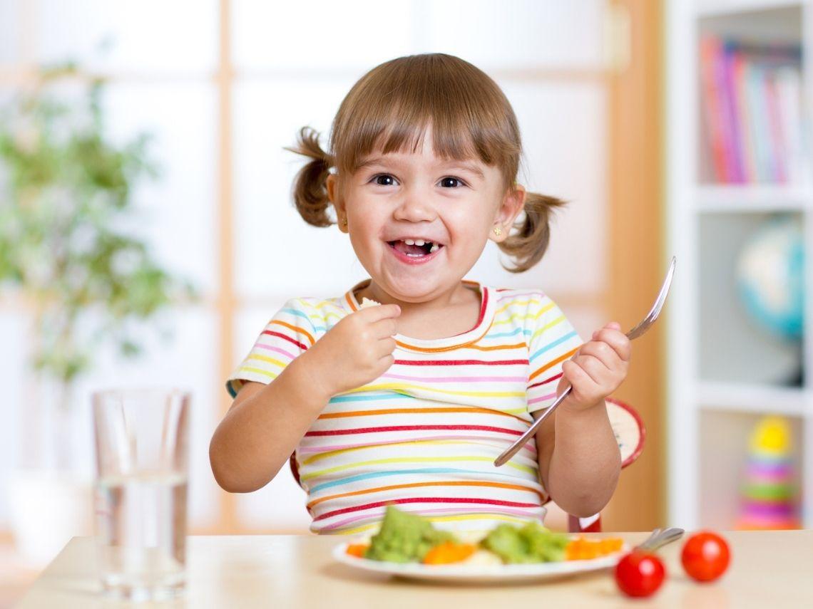 niña con comida para niños